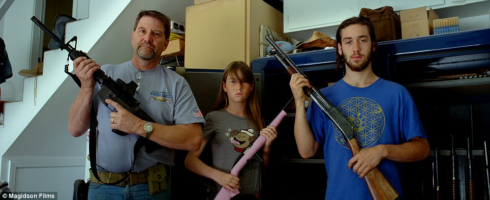 Modern family: An American family poses for a portrait holding their rifles; the young girl holds one in pale pink
